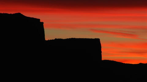 A red sky silhouettes buttes in the American Southwest Footage