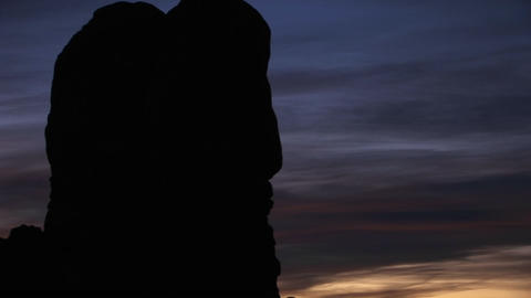 A dark sky silhouettes a hanging rock formation in Arches National Park, Utah Footage