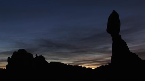 Balanced Rock is silhouetted against the golden-hour sky in Arches National Park, Utah Footage