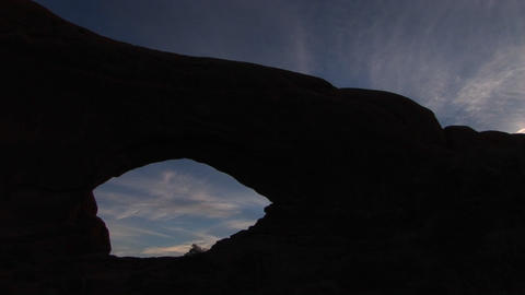 An arch is silhouetted against the sky at Arches National Park, Utah Footage