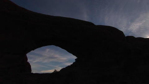 An arch is silhouetted against the sky at Arches National... Stock Video Footage