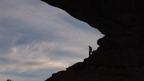 A hiker reaches the top of a rocky slope Stock Video Footage