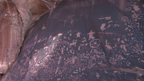 Pan-right across ancient American Indian petroglyphs at Newspaper Rock, Utah Footage