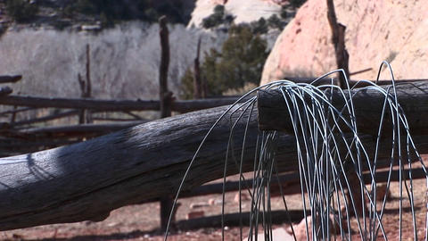 Close-up of an old gray fence with wire hanging from a log Footage