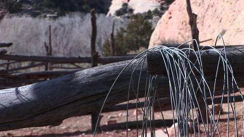 Close-up of an old gray fence with wire hanging from a log Stock Video Footage