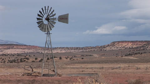 Medium shot of an old windmill standing on a desert plain Footage