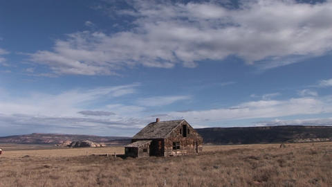 Long shot of an old abandoned homestead in the middle of a lonely prairie Footage