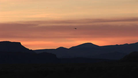 Long shot of a helicopter flying over low hills at golden-hour Footage