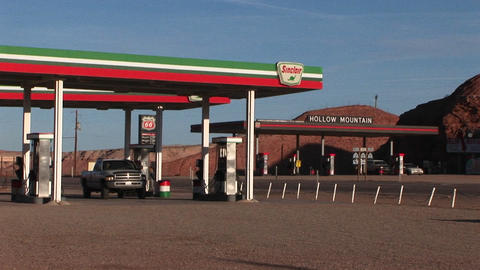 Medium shot of a pickup truck leaving a desert gas station Stock Video Footage