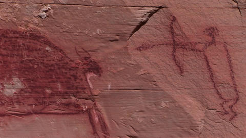 A slow pan across mysterious petroglyphs in the Southwest desert of the USA showing early man killin Footage