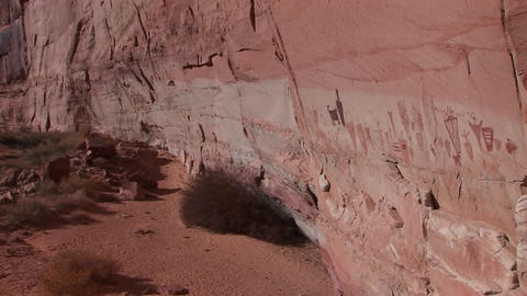 Pan-right slowly across the face of a remote canyon cliff with American Indian pictographs Footage