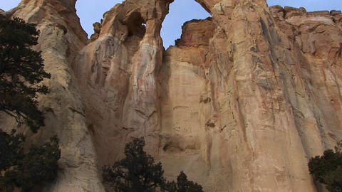 Pan-up from a hiker to an enormous stone arch in Southern Utah Footage