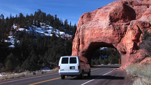 Medium shot of a car passing through an arch over the highway near Zion National Park in Utah Footage