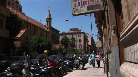 Women walk by motorcycles lined near a sidewalk and old... Stock Video Footage