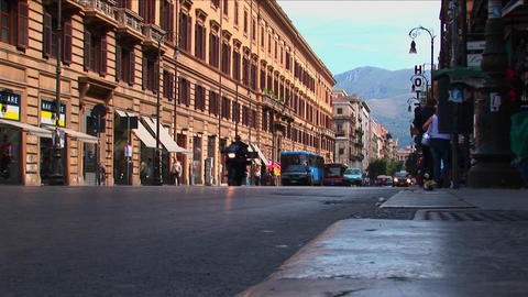 Old buildings line a busy street with vehicles and pedestrians passing through Palermo, Italy Footage