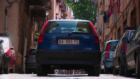 A street between apartment buildings and vehicles Palermo, Italy Footage
