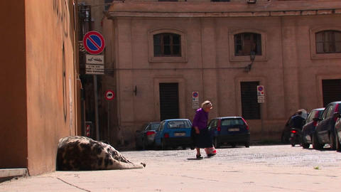 An old woman walks pass a large body mass lying against a... Stock Video Footage