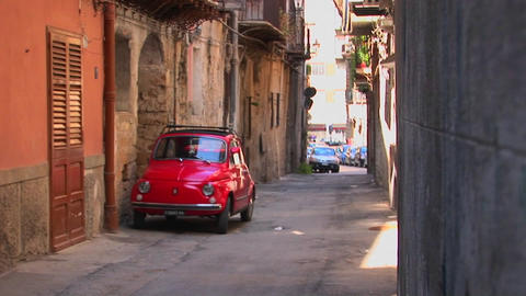 Cars parked along stone buildings in a tightly spaced alley Palermo, Italy Footage
