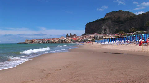 Umbrellas rest on a beach near houses and waves breaking in Cefalu, Italy Footage