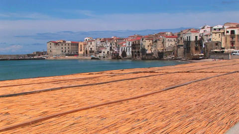 A combed beach near houses along a shoreline in Cefalu, Italy Live Action