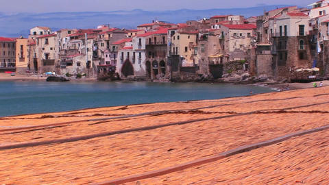 A combed beach near houses along a shoreline in Cefalu, Italy Footage