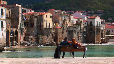 A couple sits on a bench overlooking the ocean and houses in Cefalu, Italy Footage