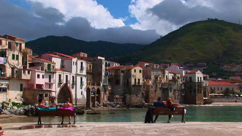 couples sit on a benches overlooking the ocean and houses in Cefalu, Italy Footage