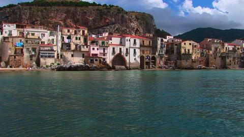 Ocean water near beach houses in Cefalu, Italy Footage