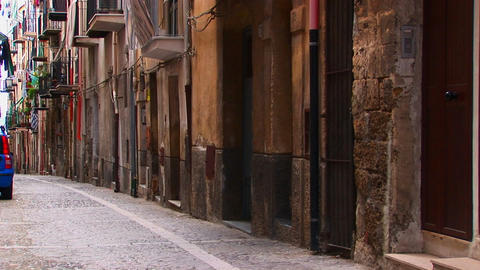 A rock street near closely placed houses and balconies in Cefalu, Italy Footage