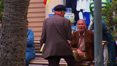 People shop and walk pass two men having a discussion in... Stock Video Footage