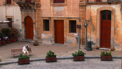 A man sits on a bench next to brick buildings within close proximity of one another in Cefalu, Italy Footage