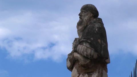 A cloudy blue sky above the statue of a man in Cefalu, Italy Footage