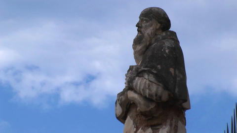 A cloudy blue sky above the statue of a man in Cefalu, Italy Stock Video Footage