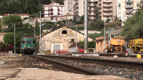A train passes through a train yard and town Stock Video Footage