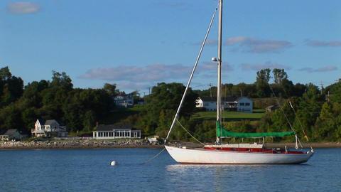 A sailboat anchored in reflective waters near shore in Maine Footage