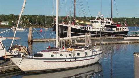 Sailboats and a sailing ship tied to docks in Maine Stock Video Footage