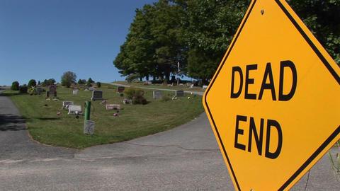 A dead end sign near a cemetery on a hillside Stock Video Footage