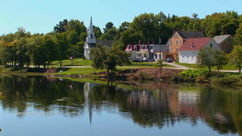 A lake reflects a peaceful New England, Maine town Stock Video Footage