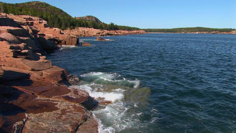 Water crashes against rocks that are near trees and a mountain range in Acadia National Park in Main Footage