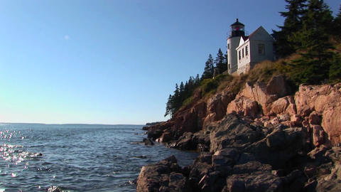 A lighthouse on the edge of a cliff overlooking the ocean in Bass Harbor Lighthouse, Maine Footage
