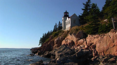 A lighthouse on the edge of a cliff overlooking the ocean... Stock Video Footage