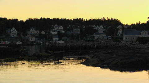 A lobster village is on a mountainside near the silhouette of reflective waters in Stonington, Maine Footage
