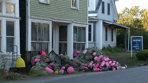 Fishing nets and buoys are in piles outside a building at... Stock Video Footage