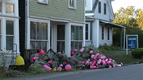 Fishing nets and buoys are in piles outside a building at a lobster village in Stonington, Maine Footage