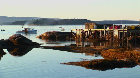 An anchored boat floats near a lobster village in Stonington, Maine at sunset Footage