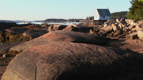 A building in a lobster village is over water as seen from a rocky shore in Stonington, Maine Footage