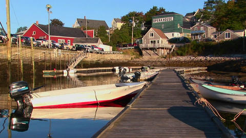 Boats are tied to a dock leading to a lobster village in Stonington, Maine Footage
