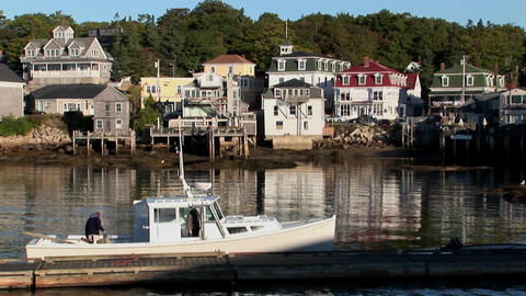 A man boards a small ship that leaves a dock near a lobster village in Stonington, Maine Footage
