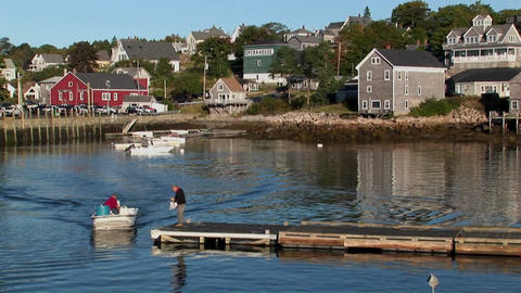 A small boat picks up a man from a dock near a lobster... Stock Video Footage