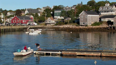 A small boat picks up a man from a dock near a lobster village in Stonington, Maine Footage
